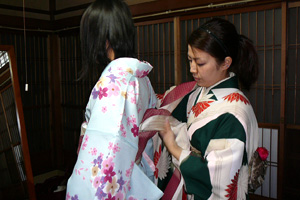 The clerk dresses the kimono to you.